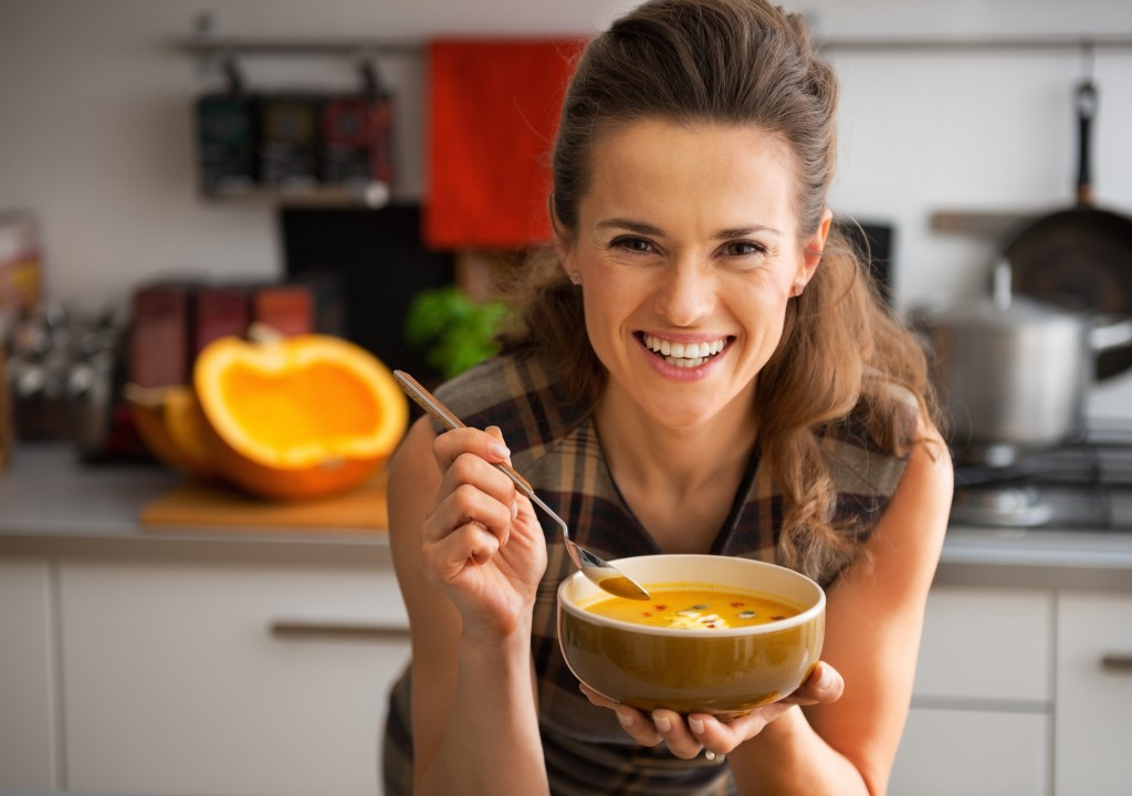 Happy young woman eating pumpkin soup in kitchen