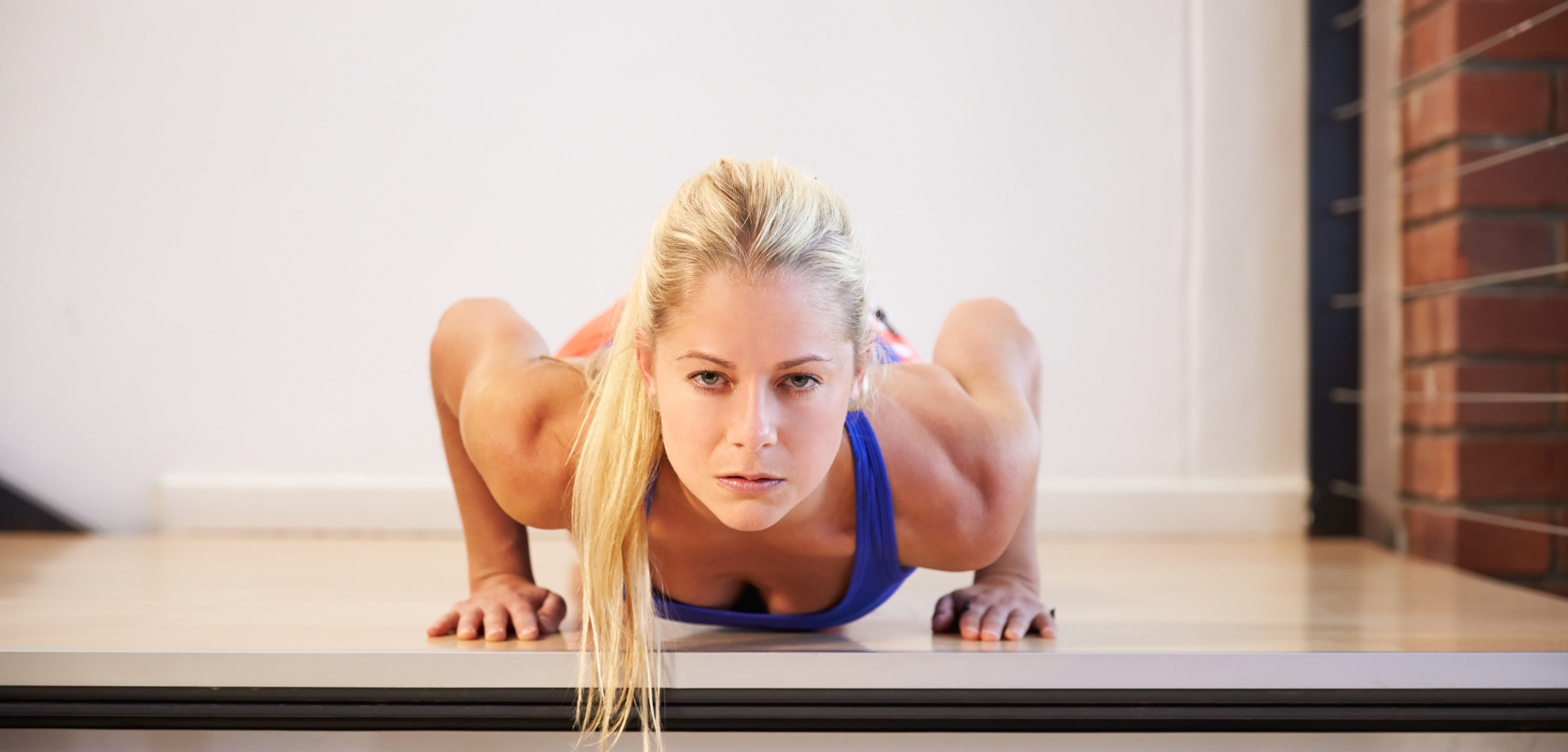 Woman In Gym Doing Press-Ups On Step Labeled Strength